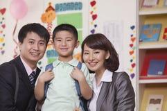 Föräldrar med deras son i klassrum Royaltyfria Bilder