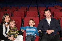 Föräldrar med deras två söner i bio Arkivbild
