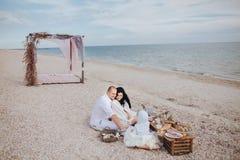 Föräldrar med ett barn sitter ashore havet Arkivbilder