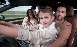Föräldrar med unga barn som sitter i bilen royaltyfria bilder