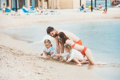 Föräldrar och barn för familjsemester på dagen för sommar för havskust Arkivbild