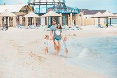 Föräldrar och barn för familjsemester på dagen för sommar för havskust Royaltyfri Bild