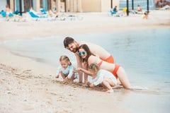 Föräldrar och barn för familjsemester på dagen för sommar för havskust Arkivbilder
