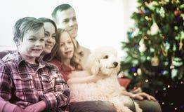 Föräldrar och barn som är lyckliga att spendera jul tillsammans Arkivfoto