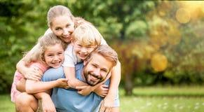 Föräldrar och barn som den lyckliga familjen royaltyfri foto