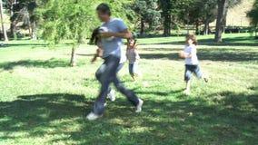 Föräldrar och barn som spelar i en parkera med en boll arkivfilmer