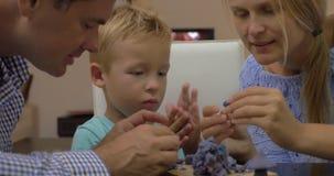 Föräldrar och barn som spelar med plasticine stock video