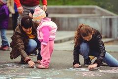 Föräldrar och barnmålarfärg på asfalt Royaltyfri Foto