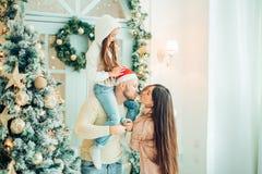 Föräldrar och behandla som ett barn ha den roliga near julgranen Älska familjen vid julgranen royaltyfri fotografi
