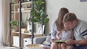 Föräldrar och den lilla dottern spelar en framkallande lek på minnestavlan lager videofilmer