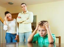 Föräldrar och den tonåriga sonen efter grälar hemma royaltyfria bilder