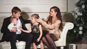 Föräldrar och deras lilla barn sitter på soffan nära den dekorerade julgranen stock video