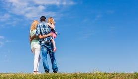 Föräldrar och dotter, arm i arm i tillbaka sikt Arkivfoto