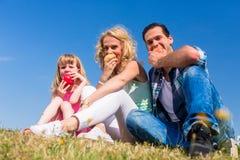Föräldrar och dotter som äter äpplen Arkivbilder