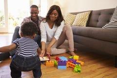 Föräldrar och son som hemma spelar med leksaker på golv royaltyfria bilder
