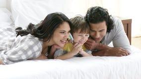 Föräldrar och son som lyssnar till musik lager videofilmer