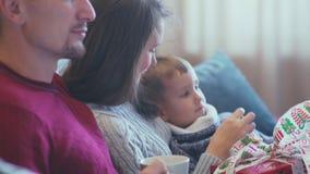 Föräldrar och sonsammanträde på en soffa i inre jul arkivfilmer