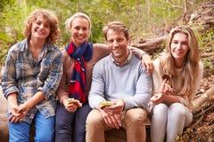 Föräldrar och tonårs- ungar som utomhus äter i en skog, stående royaltyfria bilder