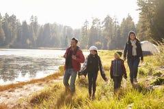 Föräldrar och två barn som går nära en sjö, slut upp arkivbilder