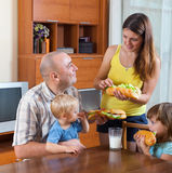 Föräldrar och två barn som har lunch Arkivfoto