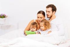 Föräldrar och två gulliga ungar spelar med minnestavlan på säng fotografering för bildbyråer