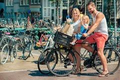 Föräldrar på cyklar på gatorna av Amsterdam Arkivbild