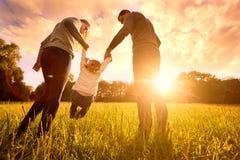 Föräldrar rymmer baby'sens händer Lycklig familj i parkeraaftonen royaltyfri fotografi