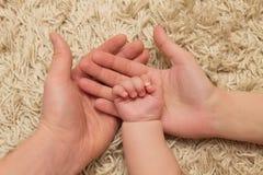 Föräldrar rymmer barnets hand Arkivbilder