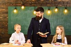 Föräldrar sätter vanligt deras ungar in i akademisk coachning Uppmärksamma studenter som skriver något i deras anteckningsböcker  royaltyfri foto
