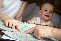 Föräldrar söker efter något på ett kort som är utbrett på suitcas för en väg Arkivfoto