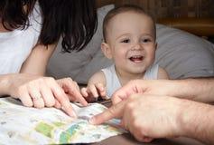 Föräldrar söker efter något på ett kort som är utbrett på suitcas för en väg Royaltyfria Foton
