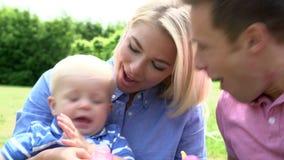 Föräldrar som blåser bubblor för ung pojke i trädgård lager videofilmer