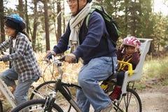 Föräldrar som cyklar i en skog med litet barndottern, slut upp royaltyfri fotografi