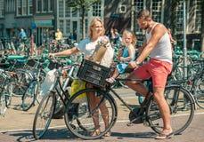Föräldrar som cyklar på gatorna av Amsterdam Royaltyfria Bilder