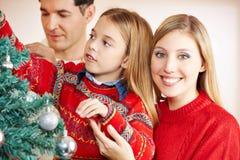 Föräldrar som dekorerar julträdet Royaltyfria Bilder