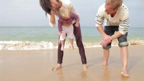 Föräldrar som doppar dottertår in i havet stock video
