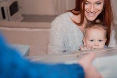 Föräldrar som ger en gåva till deras lilla son för jul royaltyfri bild