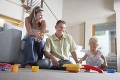 Föräldrar som håller ögonen på sonen spela med leksaken Arkivfoton