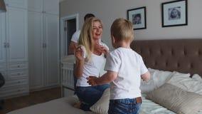 Föräldrar som har gyckel med deras lilla dotter på säng Familj som spenderar tid på morgonen lager videofilmer