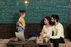 Föräldrar som hemma undervisar ungen Pojke som framlägger hans kunskap till mamman och farsan Föräldrar som lyssnar deras son, sv Royaltyfri Fotografi