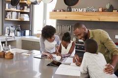 Föräldrar som hjälper barn med läxa i kök royaltyfria foton