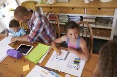 Föräldrar som hjälper barn med läxa på tabellen arkivfoton