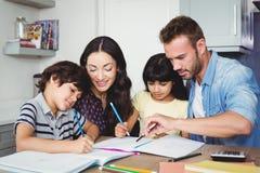 Föräldrar som hjälper barn som gör läxa arkivfoton