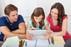 Föräldrar som hjälper dottern, i att använda den digitala minnestavlan Arkivbilder
