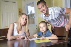 Föräldrar som hjälper sonen med läxa i hemmiljö Arkivbilder