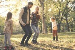 Föräldrar som in hoppar över rep för liten flicka för hopprep hållande arkivfoton