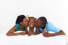 Föräldrar som kysser dottern Arkivbilder