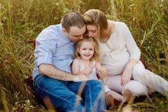 Föräldrar som kysser dottern på naturen, lycklig familj, leende Arkivbild