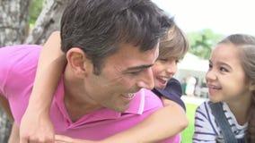 Föräldrar som på ryggen ger ritt för barn i trädgård