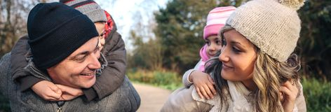 Föräldrar som på ryggen utomhus ger ritt till lyckliga barn arkivfoto